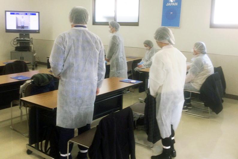 帽子と白衣を身に着けた訓練生達
